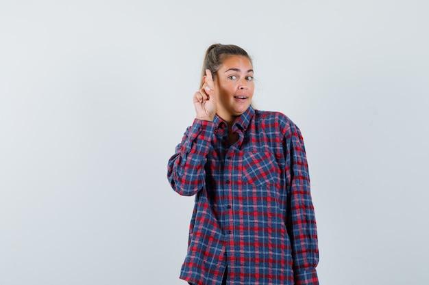 가리키는 및 지능형, 전면보기를 찾고 체크 셔츠에 젊은 아가씨.