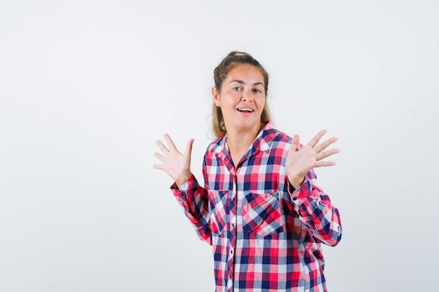 手のひらを見せながら、至福の正面図を見てポーズをとるチェックシャツの若い女性。