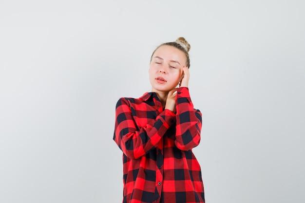 서서 멋진 찾고있는 동안 포즈를 취하는 체크 셔츠에 젊은 아가씨