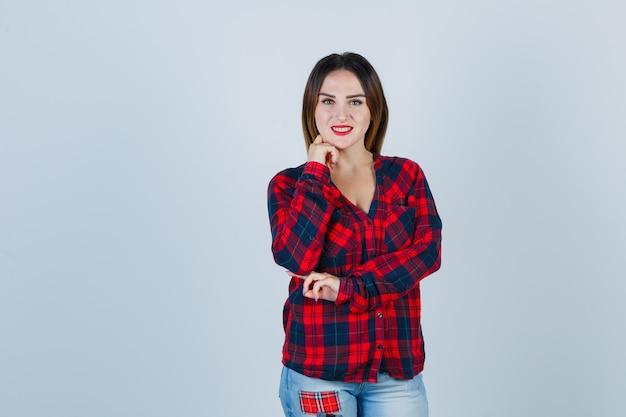 手に顎を支え、陽気に見えるチェックシャツの若い女性、正面図。