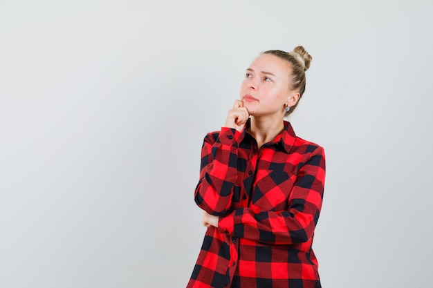 Молодая дама в клетчатой рубашке подпирает подбородок рукой и смотрит задумчиво