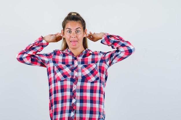 Молодая дама в клетчатой рубашке опускает мочки ушей и выглядит забавно, вид спереди.