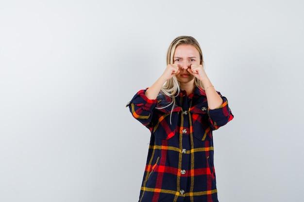 Девушка в клетчатой рубашке протирает глаза и обиженно смотрит, вид спереди.