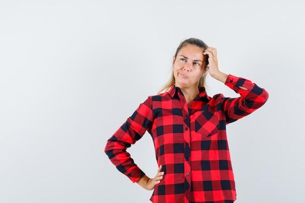 Девушка в клетчатой рубашке почесывает голову и выглядит нерешительно