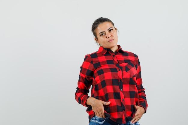 체크 셔츠에 젊은 아가씨, 반바지 주머니에 손을 잡고 자신감을 찾고