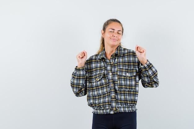체크 셔츠에 젊은 아가씨, 우승자 제스처를 보여주는 반바지, 평화로운, 전면보기.