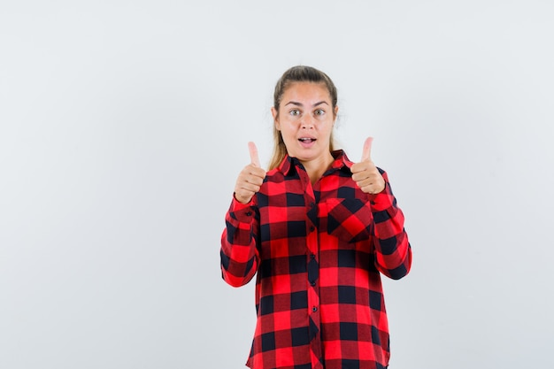 チェックシャツを着た若い女性が二重の親指を立てて驚いているように見える