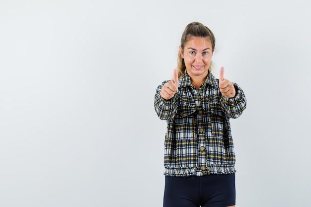 チェックシャツを着た若い女性は、二重の親指を立てて自信を持って、正面図を示しています。