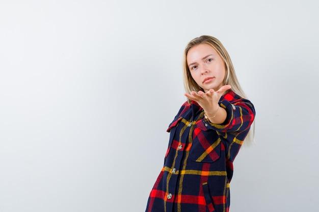 チェックシャツを着た若い女性は、ジェスチャーを与え、自信を持って、正面図を示しています。
