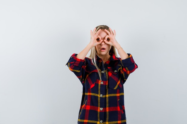 Молодая дама в клетчатой рубашке показывает жест в очках и изумленно смотрит, вид спереди.