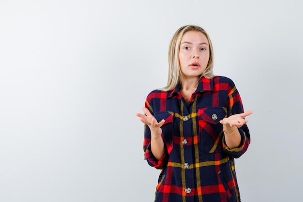 無力なジェスチャーを示し、困惑している、正面図を示すチェックシャツの若い女性。