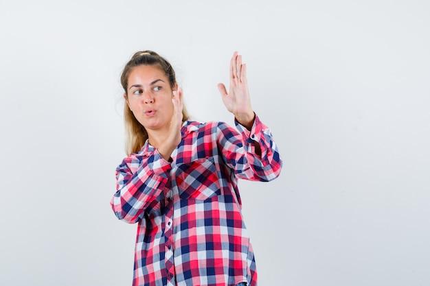 가라테 절단 제스처를 보여주는 체크 셔츠에 젊은 아가씨와 강력한 전면보기를 찾고 있습니다.