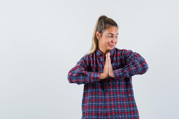 ナマステのジェスチャーを示し、希望に満ちた正面図を示すチェックシャツの若い女性。