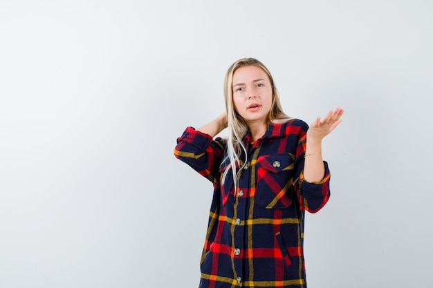 뭔가 표시 하 고 주저, 전면보기를 찾고 체크 셔츠에 젊은 아가씨.