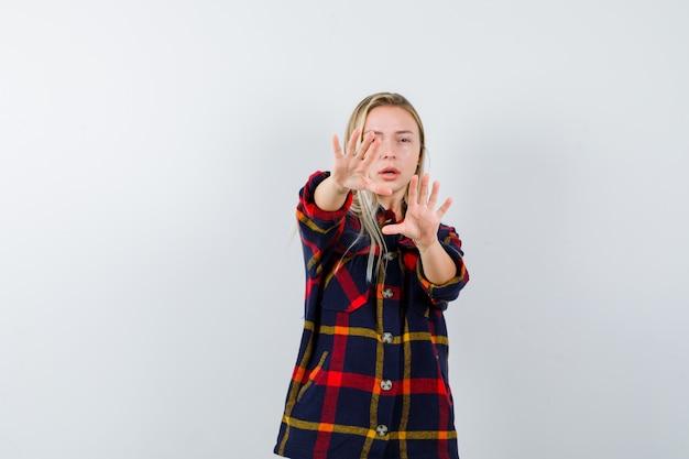 Молодая дама в клетчатой рубашке показывает жест стоп и выглядит испуганной, вид спереди.