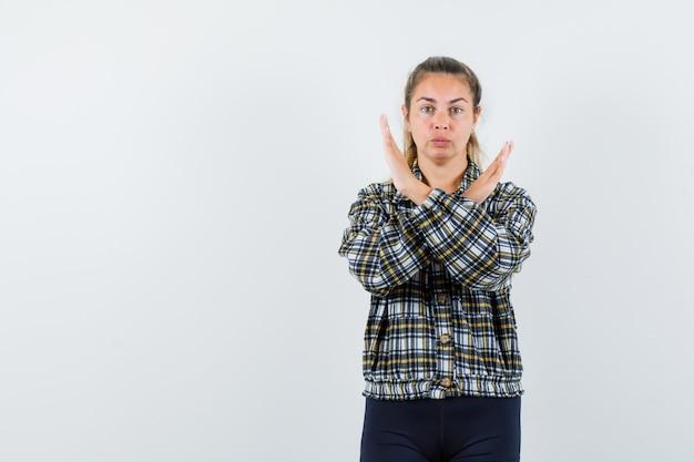 停止ジェスチャーを示し、真剣に見えるチェックシャツの若い女性、正面図。