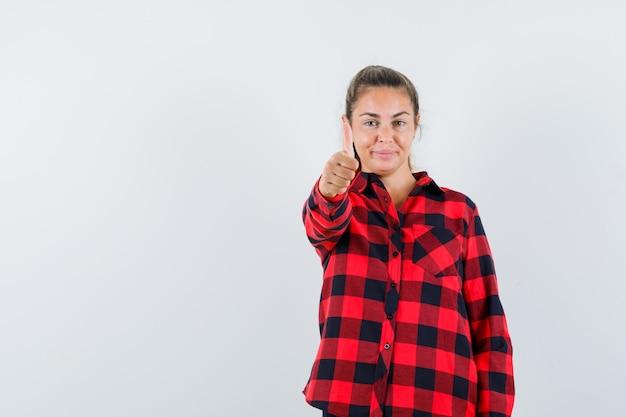 엄지 손가락을 표시 하 고 기분 좋은 찾고 체크 셔츠에 젊은 아가씨 무료 사진