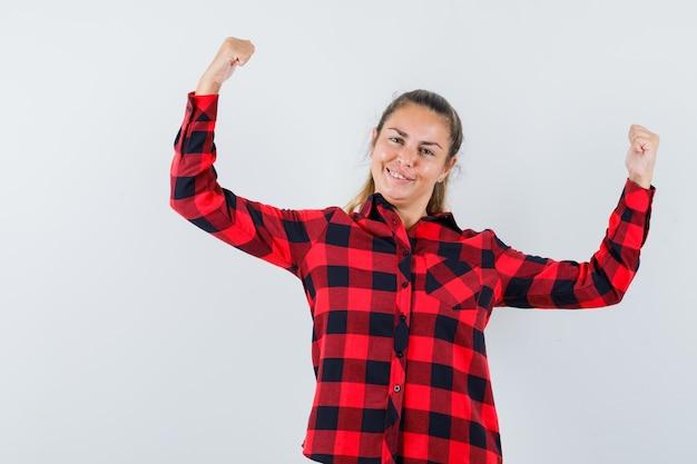 체크 셔츠 승자 제스처를 보여주는 행복 찾고 젊은 아가씨
