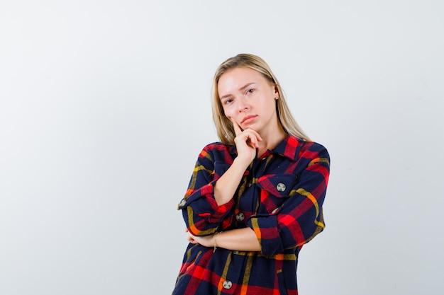 생각 포즈에 서 있고 자신감, 전면보기를 찾고 체크 셔츠에 젊은 아가씨.