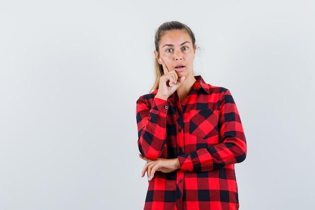 Молодая дама в клетчатой рубашке стоит в позе мышления и выглядит удивленно