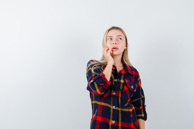 찾고 우유부단, 전면보기 동안 생각 포즈에 서있는 체크 셔츠에 젊은 아가씨.