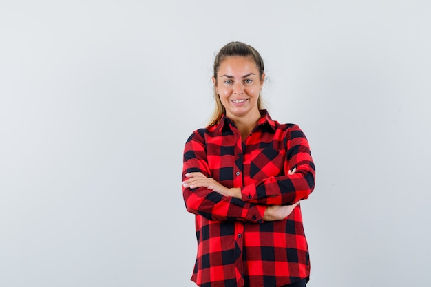 腕を組んで立って陽気に見えるチェックシャツの若い女性