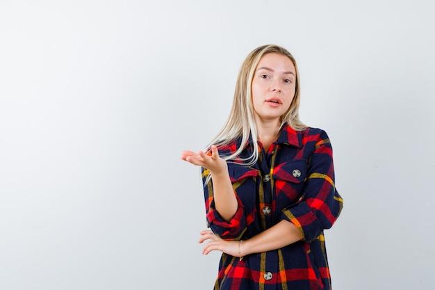 チェックシャツを着た若い女性は、ジェスチャーを質問し、無力に見える、正面図で手を伸ばしています。