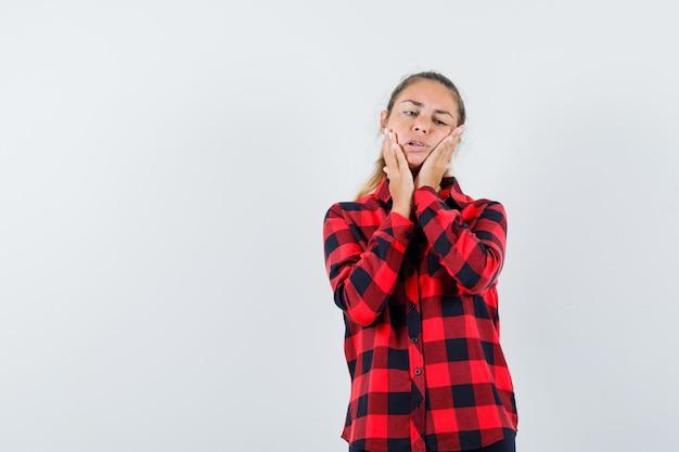 체크 셔츠를 입은 젊은 아가씨가 치통으로 고통 받고 불편 해 보입니다.