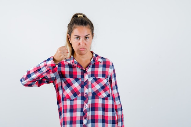 주먹으로 위협 하 고 엄격한 전면보기를 찾고 체크 셔츠에 젊은 아가씨.