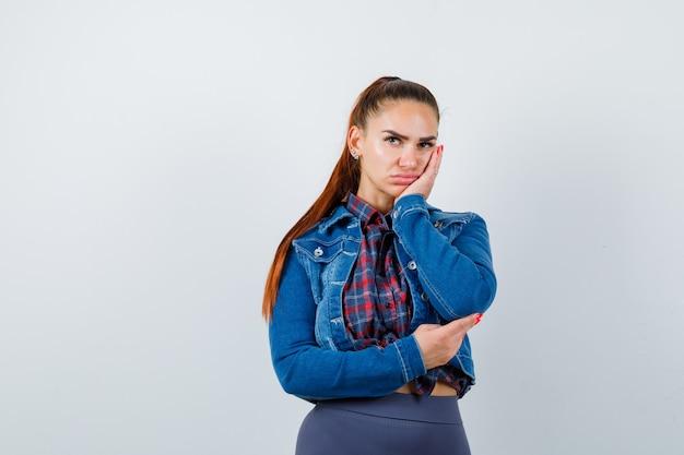 Молодая леди в клетчатой рубашке, джинсовой куртке, прислонившейся щекой к руке и скучающей, вид спереди.