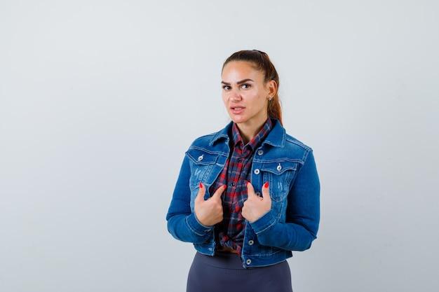 市松模様のシャツを着た若い女性、自分を指して注意深く見ているデニムジャケット、正面図。