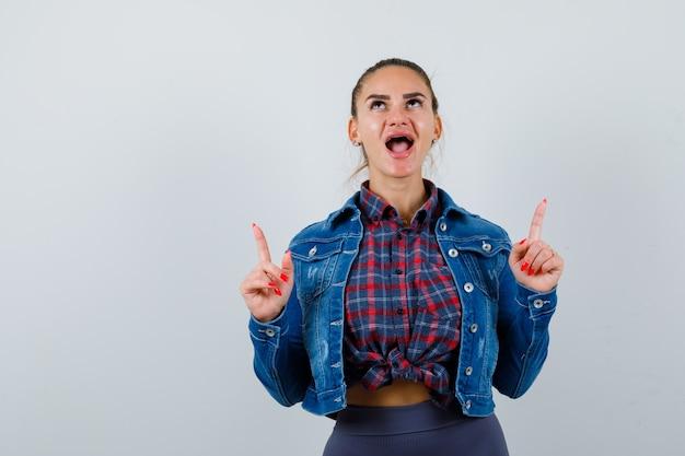 市松模様のシャツを着た若い女性、上向きで陽気に見えるデニムジャケット、正面図。