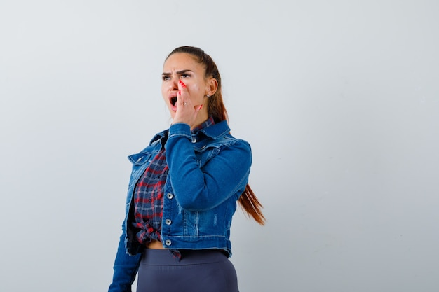市松模様のシャツを着た若い女性、口の近くに手を持って叫び、イライラしているように見えるデニムジャケット、正面図。