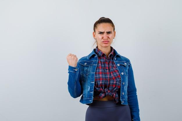 市松模様のシャツを着た若い女性、くいしばられた握りこぶしを示し、真剣に見えるデニムジャケット、正面図。