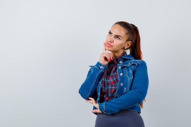 市松模様のシャツを着た若い女性、あごに指を置いたデニムジャケット、思慮深く見える、正面図。