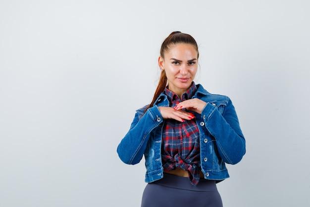 市松模様のシャツを着た若い女性、胸に手を当てて自信を持って見えるデニムジャケット、正面図。