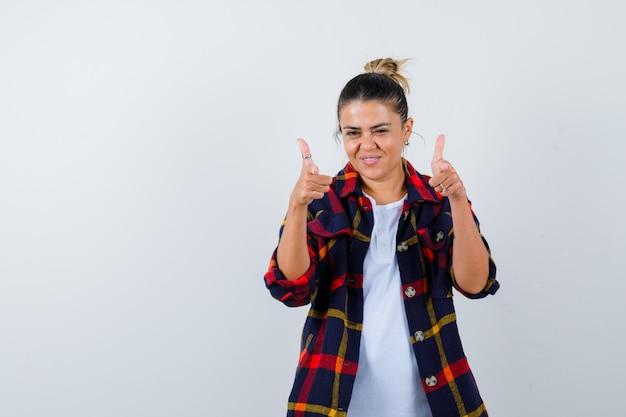 체크 무늬 셔츠 앞에 가리키는 자신감을 찾고 젊은 아가씨 무료 사진