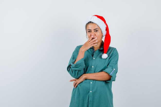 クリスマスの帽子をかぶったお嬢様、口に手を当てて困惑した様子のシャツ、正面図。