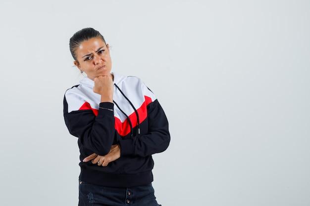 彼女の拳に寄りかかって、焦点を合わせて、正面図を探しているカラフルなスウェットシャツの若い女性。