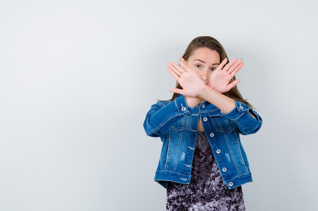 Молодая дама в платье, джинсовой куртке показывает жест отказа и выглядит стыдно, вид спереди.