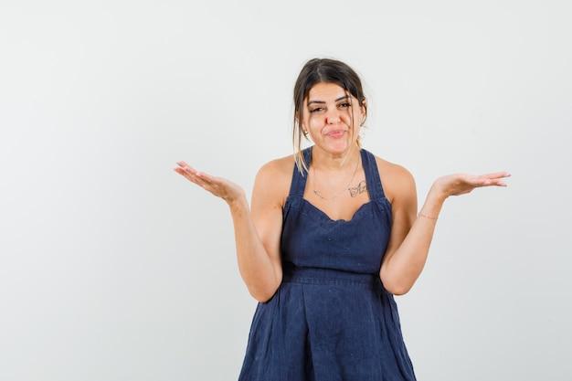 Молодая дама в платье показывает беспомощный жест и выглядит смущенным