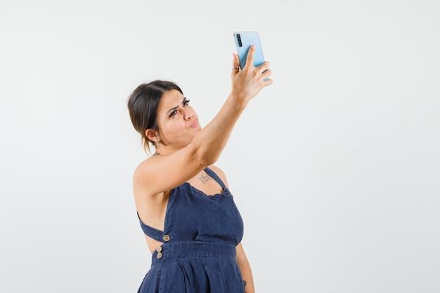 Молодая дама в платье делает селфи на мобильном телефоне и выглядит красиво