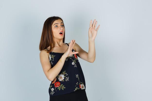 Молодая дама в цветочном топе показывает жест стоп и выглядит испуганной