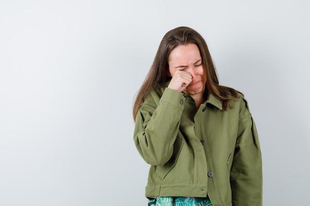 緑のジャケットを着た若い女性が泣きながら目をこすりながら落ち込んでいる、正面図。