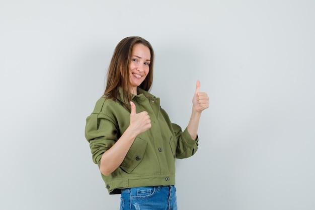 緑のジャケットのショートパンツの若い女性は、二重の親指を上げて、至福に見えます