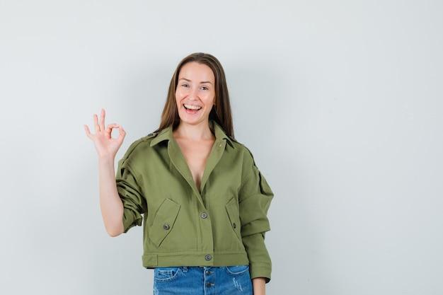 녹색 재킷에 젊은 아가씨, 확인 제스처를 표시하고 유쾌한, 전면보기를 찾고 반바지.