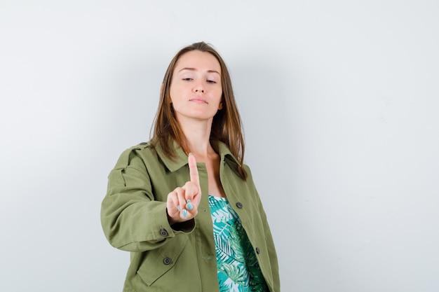 緑のジャケットを着た若い女性は、細かいジェスチャーを保持し、自信を持って、正面図を示しています。