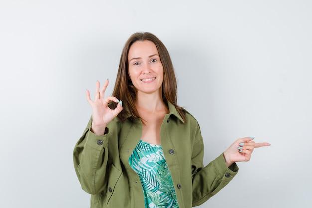 Молодая дама в зеленой куртке показывает хорошо жест, указывая вправо и выглядит довольным, вид спереди.