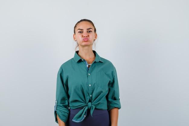 緑のシャツを着た若い女性が頬を吹いて、唇をふくれっ面し、不機嫌そうに見える、正面図。