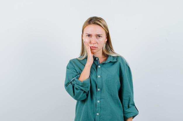 뺨에 손을 잡고 화가 찾고 녹색 셔츠에 젊은 아가씨